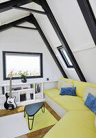 Yellow sofa in attic room with steel roof beams