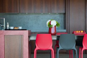 Red and black plastic chairs around table in kitchen