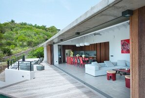 View into modern house with open wall adjoining terrace