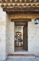 Open wooden front door of rustic stone house