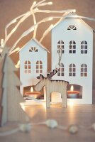 Wooden moose in front of tealights in two house-shaped lanterns