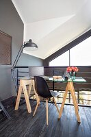 Glass desk on wooden trestles, classic chair and standard lamp on gallery