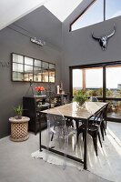 Long, industrial-style table and various chairs in high-ceilinged dining room with dark grey walls
