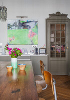 Old chairs around wooden table in front of grey kitchen counter and lattice door