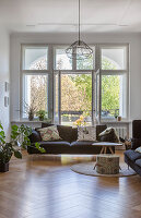 Sofa and coffee table in front of open balcony doors in period apartment