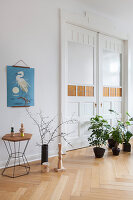 Houseplants on floor in front of closed double doors in period apartment