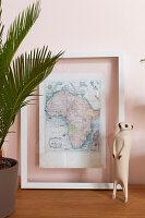 Meerkat figurine in front of framed map of Africa