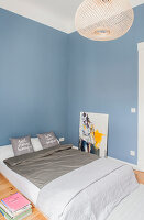 Double bed and modern art in bedroom with blue wall