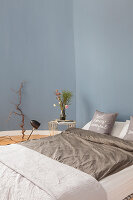 Double bed and side table in bedroom with blue walls