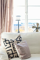 Cushion with graphic pattern in living room in pastel shades