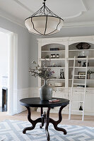 Round table in front of shelving in elegant connecting room