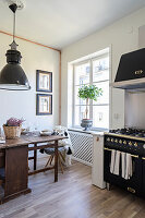 Old wooden table in front of window and gas cooker in kitchen