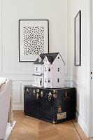 Dolls' house on old black trunk in corner