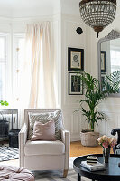 Pale armchair in elegant living room with panelled walls
