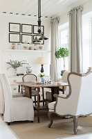Various chairs and armchairs around wooden table in dining room