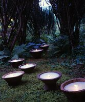 Large candles in wooden bowls amongst moss and ferns in garden