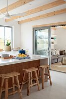 Rustic bar stools at white kitchen counter with view into living area