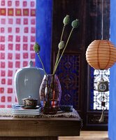 Vase of poppy seed heads next to china jar and lantern