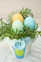 Coloured Easter eggs nestling in fresh rosemary in an Easter flowerpot