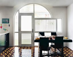 Black chairs and set table on geometric floor tiles in dining area in front of glazed arch with glass door