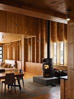 Black wood-burning stove on stone plinth in wooden house