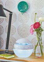 A ranunculus bouquet, an air humidifier and a lamp on a bedside table in front of patterned wallpaper