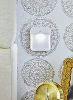 A night light on patterned wallpaper next to a headboard