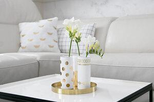 Goldfarbenes Tablett mit eleganten DIY-Blumenvasen auf Couchtisch