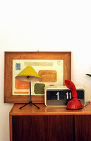 Retro radio, telephone, table lamp and framed picture on sideboard