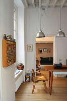 Table and classic chair below pendant lamp in period apartment