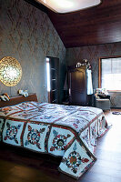 Quilt on bed in bedroom with dark ornate wallpaper