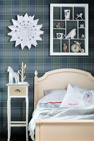 Display case on blue tartan wallpaper in vintage-style child's bedroom