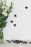 Black artificial flowers next to vase of white Eustomas