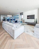 Pale sofa in open-plan elegant interior