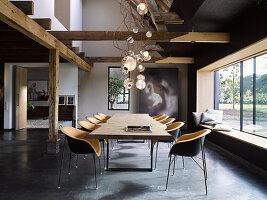 Maßgefertigter Esstisch mit Designerstühlen vor Fensterfront in offenem Wohnraum