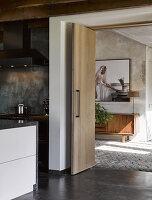 Blick durch offene Schiebefalttür auf Sideboard und Foto im Vorraum