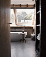 Free-standing bathtub below window on concrete floor in attic bethroom