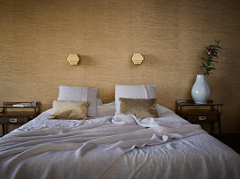 Double bed, bedside tables and lamps mounted on wall covered in elegant wallpaper