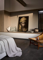 Large photo on masonry ledge and vintage chair in bedroom with dark wooden floor