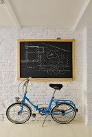 Blue folding bike below architect's plan on chalkboard