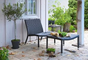 Modern poly-rattan armchair and footstool on terrace