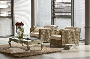Two wicker armchair and metal coffee table in modern loft apartment