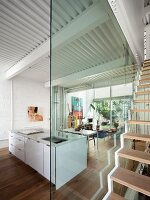 Glass wall in open-plan interior with island counter and floating staircase