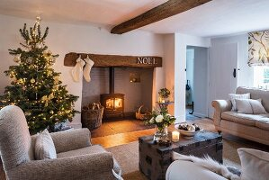 Christmas tree and fire in log burner in cosy living room