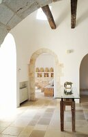 Foyer with arched doorways and glass-topped table with wooden base in foyer of trullo