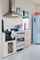 Old wood-fired cooker next to modern cooker and retro fridge