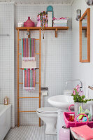 Colourful accessories in white bathroom with mosaic tiles