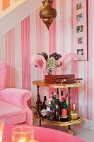 Alter Barwagen vor gestreifter Tapete im pinken Wohnzimmer