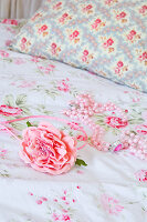 Artificial rose and string of beads on floral bedlinen