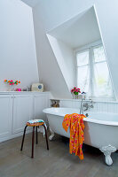 Free-standing bathtub, stool and fitted cupboards below shelf in white bathroom with dormer window